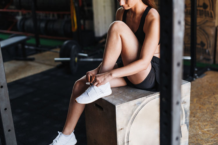 Athlete wearing sports shoe while sitting on box at gym