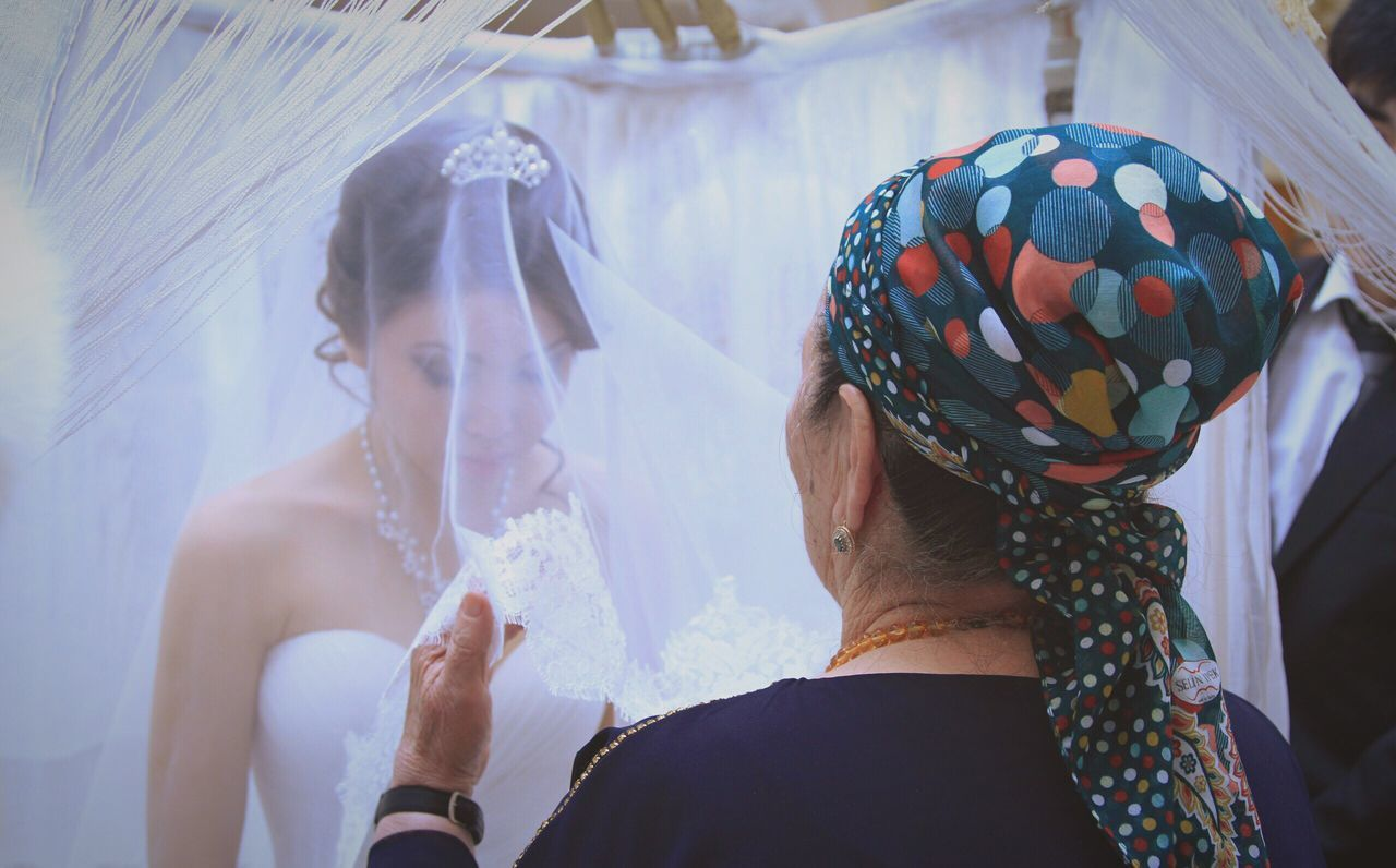 Woman adjusting veil of bride during wedding ceremony