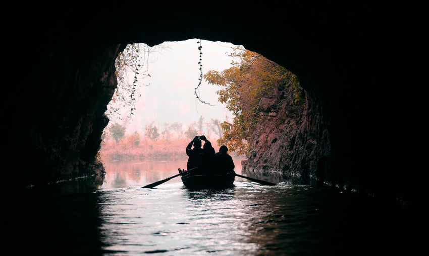 Silhouette People Boating On Lake Through Cave