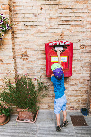 Rear view of boy putting letter in mailbox