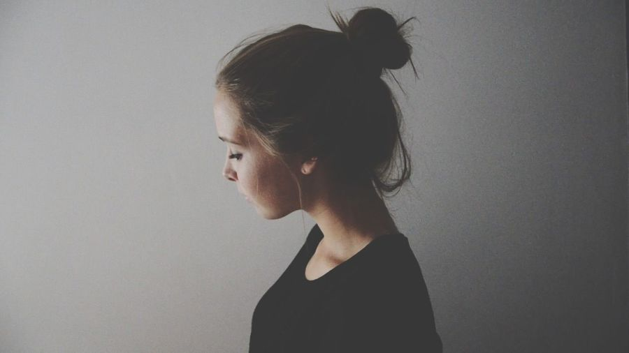 Close-up side view of a young woman over grey background