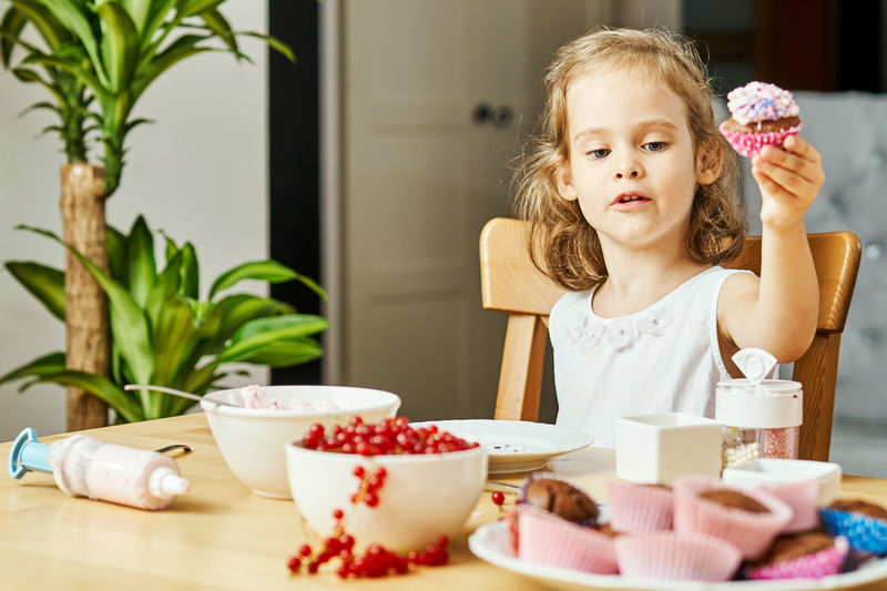 Muffin Muffins Girl Child Kid Childhood Food And Drink Food Cup Table Sweet Food Women Females One Person Sitting Front View Sweet Indoors  Girls Lifestyles Drink Innocence Mug Cute Temptation Breakfast