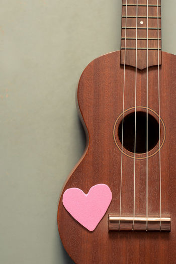 Close-up of heart shape on guitar at table
