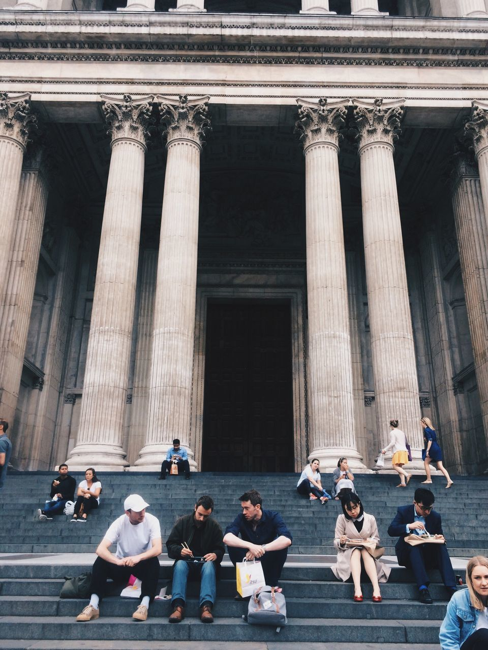 large group of people, real people, women, men, architecture, travel destinations, built structure, building exterior, architectural column, statue, tourism, mixed age range, lifestyles, outdoors, history, leisure activity, sculpture, day, sitting, group of people, city, sky, people, adult, adults only