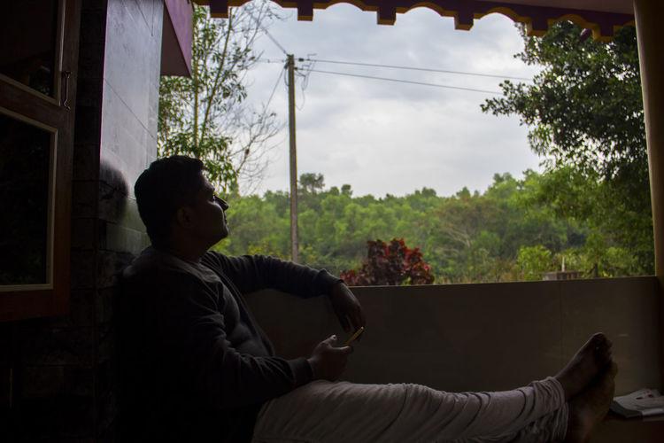 Man relaxing by window