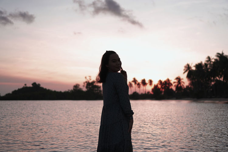 Smiling woman in silhouette at sunset