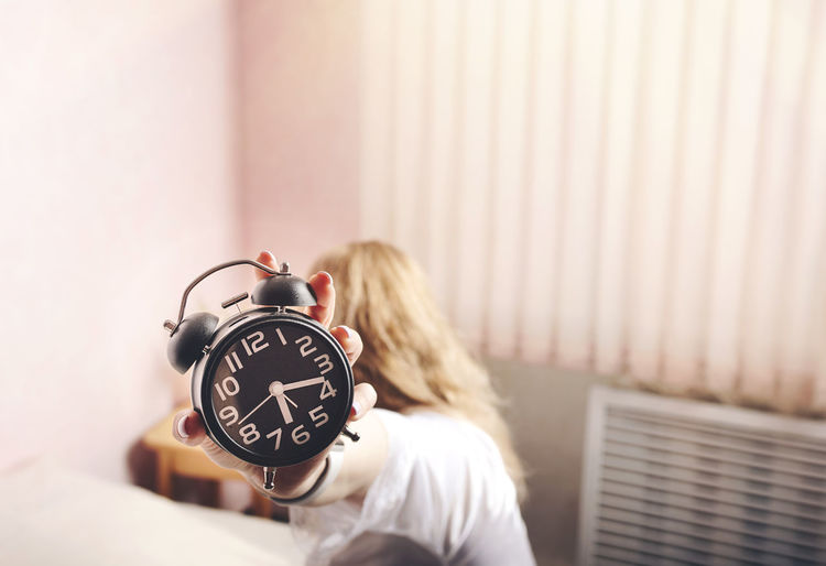 Female hand in a white bed holding an alarm clock in the morning Time Clock Alarm Clock One Person Women Indoors  Blond Hair Hair Adult Bedroom Bed Focus On Foreground Copy Space Relaxation Long Hair Young Adult Hairstyle Rear View Morning Girl International Women's Day 2019 Analogue Sound My Best Photo