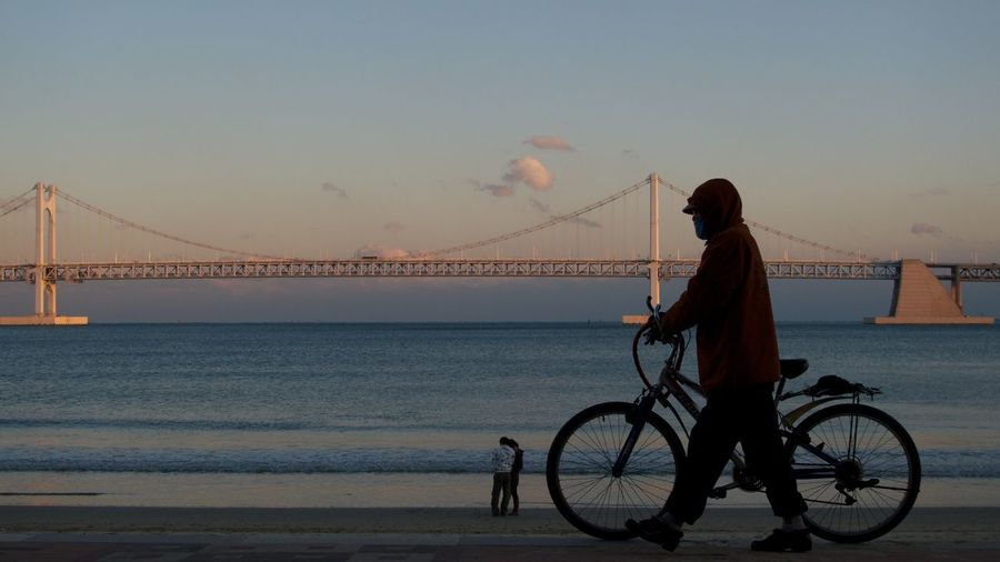 Side View Of Man With Bicycle Walking Against Bridge Over Sea
