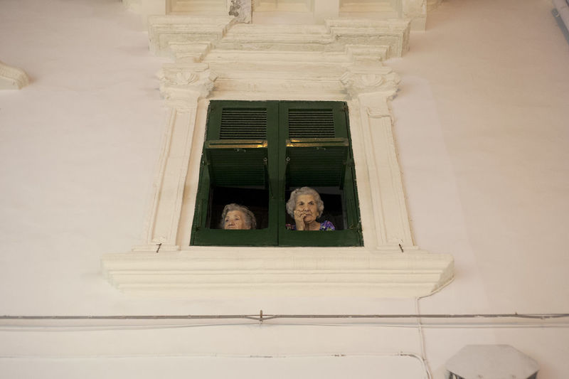 Two women spend their time looking outside their window Curiosity Night Old Buildings Oldpeople Oldwomen Overlooking Southitaly To_look_outside Window