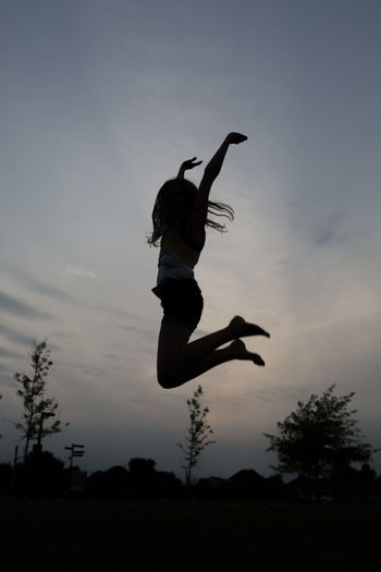 Silhouette person jumping against clear sky