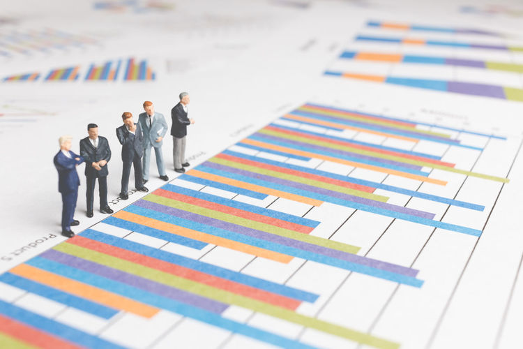 Close-up of businessmen figurines on bar graph