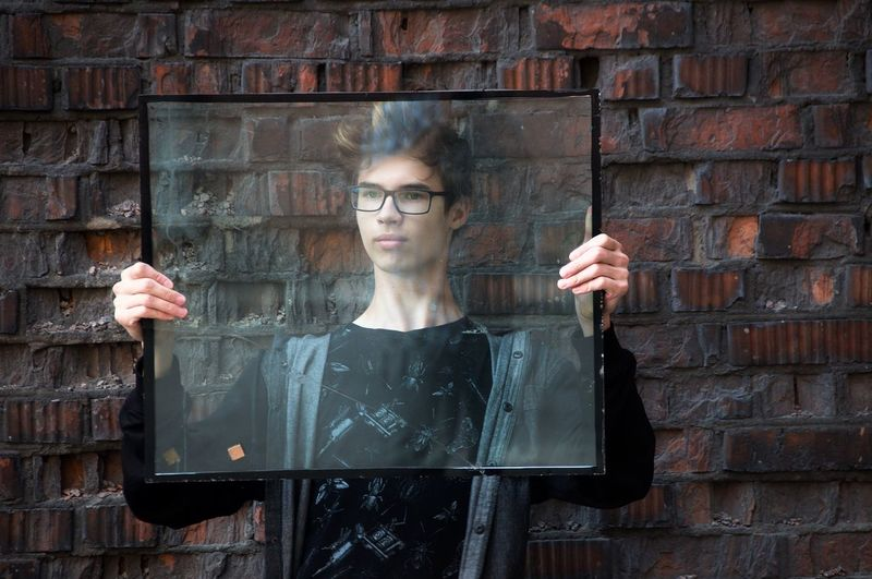 Young man holding glass against wall