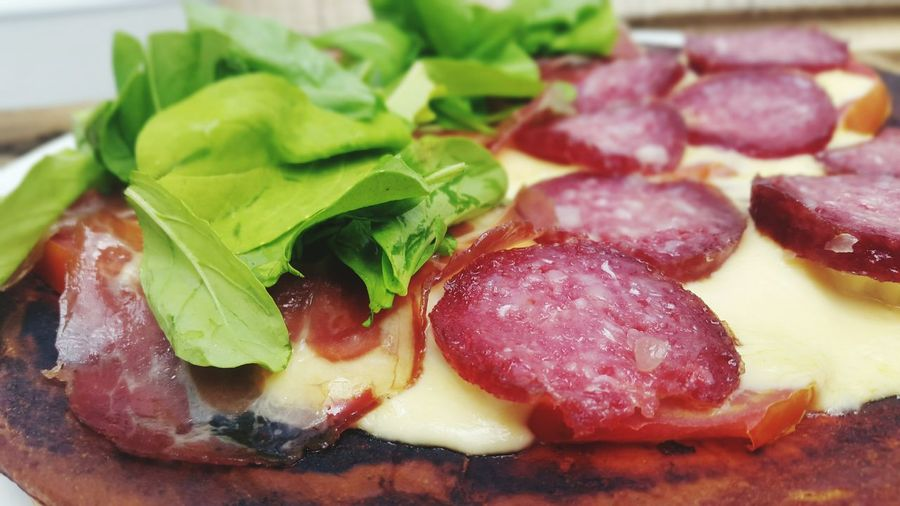 Close-Up Of Pizza With Salami And Arugula