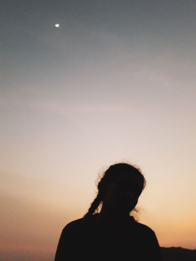 Rear view of silhouette woman against sky during sunset