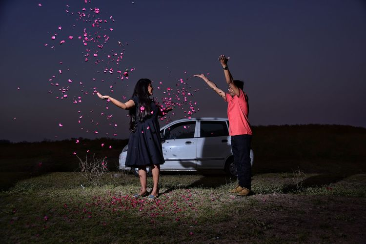 Full Length Of Young Couple Standing On Grass Field Against Sky At Night