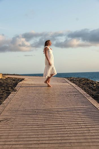 Side view of girl standing on boardwalk against sea