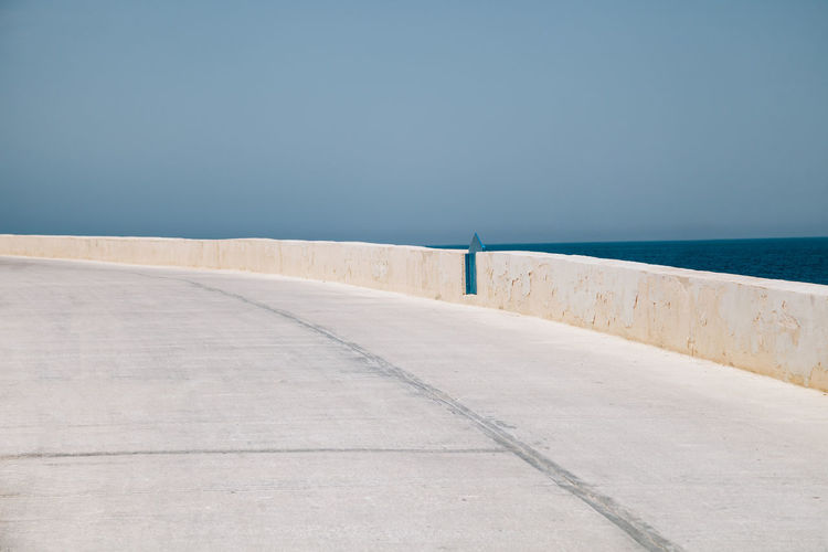 View of road by sea against sky