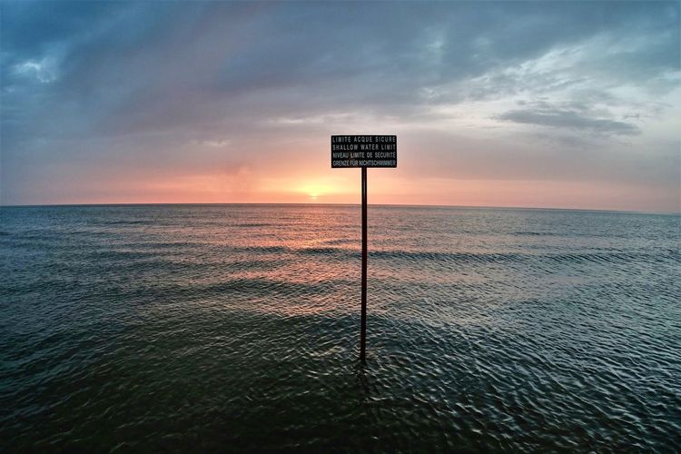Information sign by sea against sky during sunset