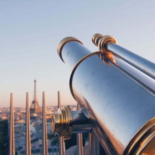 Close-up of hand-held telescope against sky in city