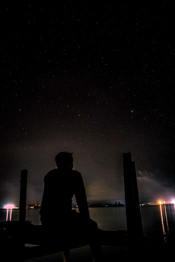 Silhouette man sitting against illuminated sky at night