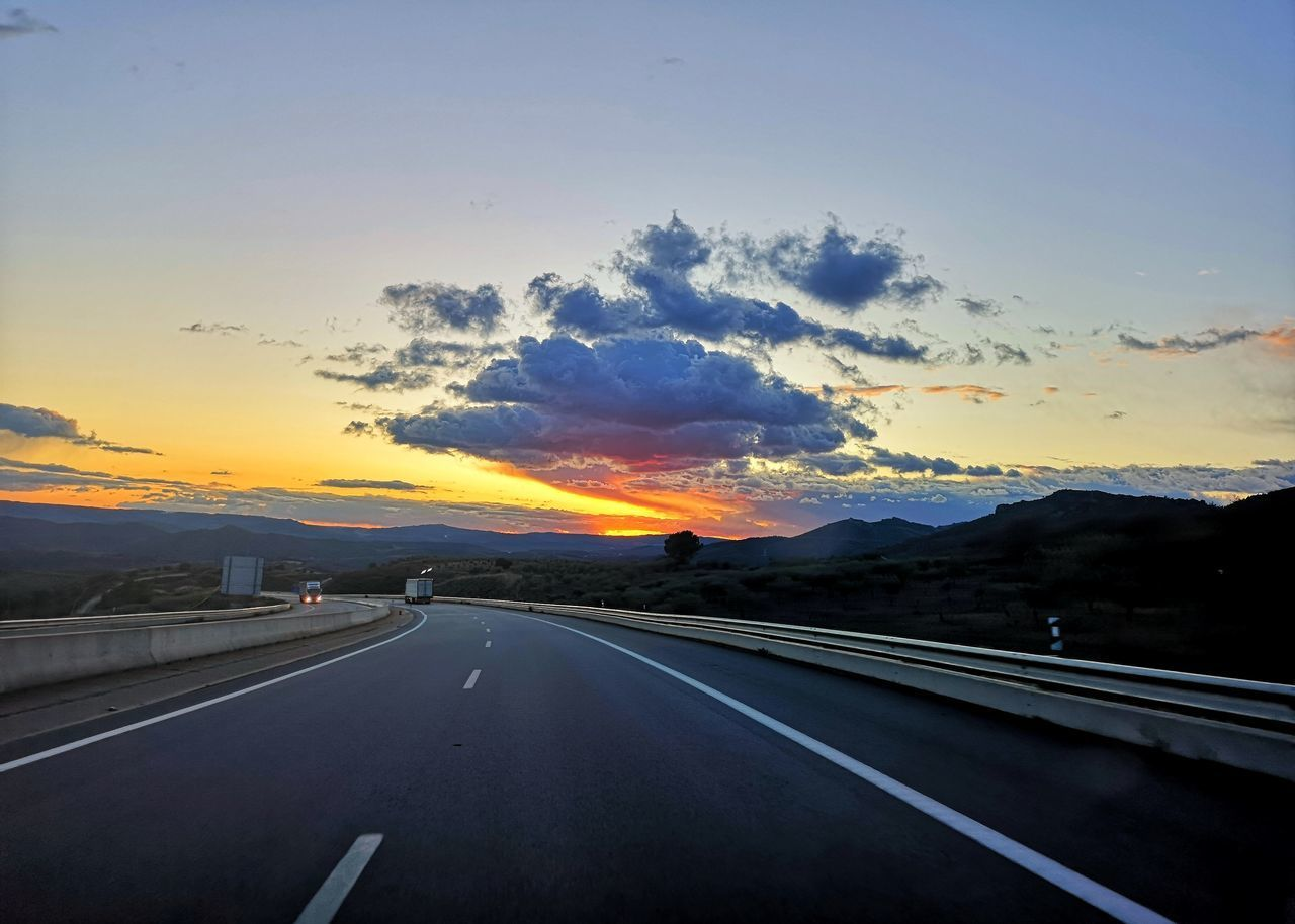 HIGHWAY AGAINST SKY AT SUNSET