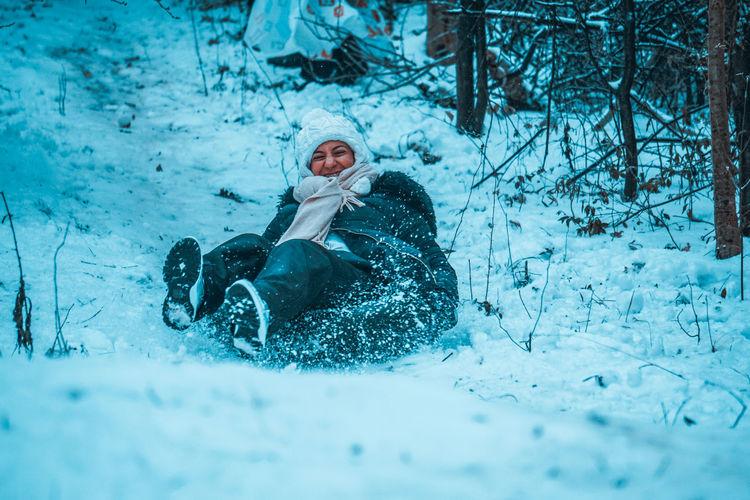 Cheerful woman sledding on snowy hill