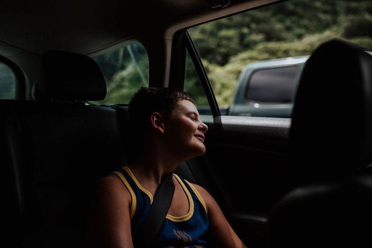 Rear view of boy looking through car