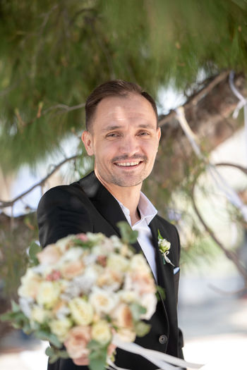 Portrait of smiling man giving bouquet standing outdoors