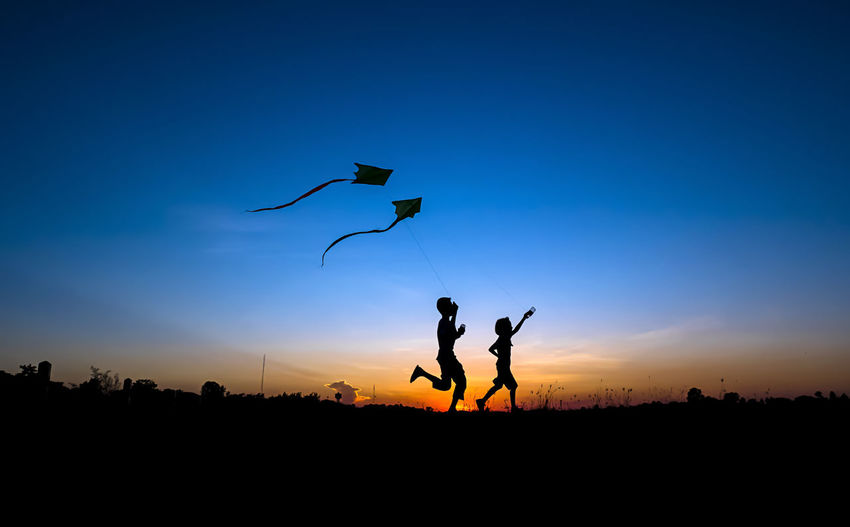 Silhouette of boy and girl flying a kite in sunset background. Happy, EyeEmNewHere Blue Flying Jumping Kite - Toy Leisure Activity Lifestyles Men Mid-air Nature Outdoor, Fly, Leisure, Fun, Natural, Boy, Laughter, Concept, Life, Field, Yellow, Holiday, Kite, Summer, People, One, Sun, Caucasian, Cute, Smile, Modern, Energy, Youth, Healthy, Girl, Young, Beach, Blue, Free, Plant, Childhood, Sunset, Sky, Kid, Looking, Outdoor, Fly, Leisure, Fun, Natural, Boy, Laughter, Concept, Life, Field, Yellow, Holiday, Kite, Summer, People, One, Sun, Caucasian, Cute, Smile, Modern, Energy, Youth, Healthy, Girl, Young, Beach, Blue, Free, Plant, Childhood, Sunset, Sky, Kid, Looking, Outdoors Parachute Paragliding People Playing Real People Silhouette Sky Sport Sunset Togetherness Mix Yourself A Good Time