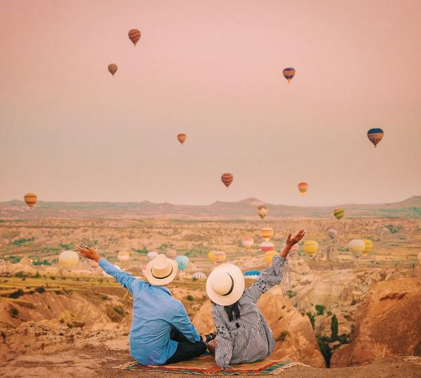 Rear View Of Couple Looking At Hot Air Balloons Flying Against Sky
