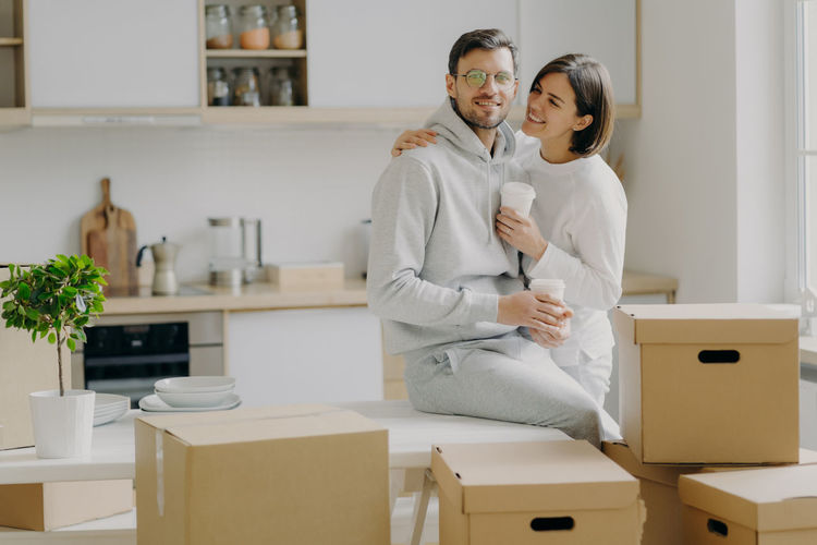 Smiling woman looking at man sitting on table