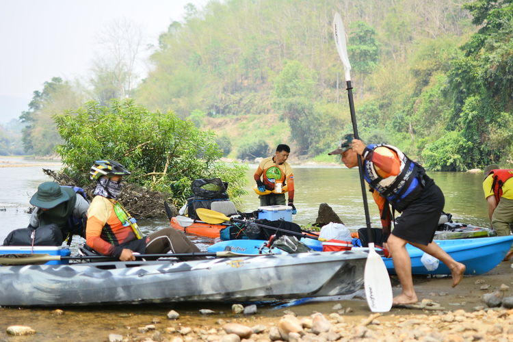 Water Outdoors Chiang Rai, Thailand Tree Group Of People Plant Nature Day Transportation Safety Real People Sport Group Medium Group Of People Men Adventure Land People Oar Nautical Vessel Adult