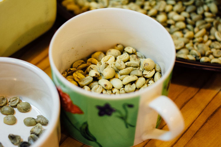 High Angle View Of Raw Coffee Beans In Cup On Table