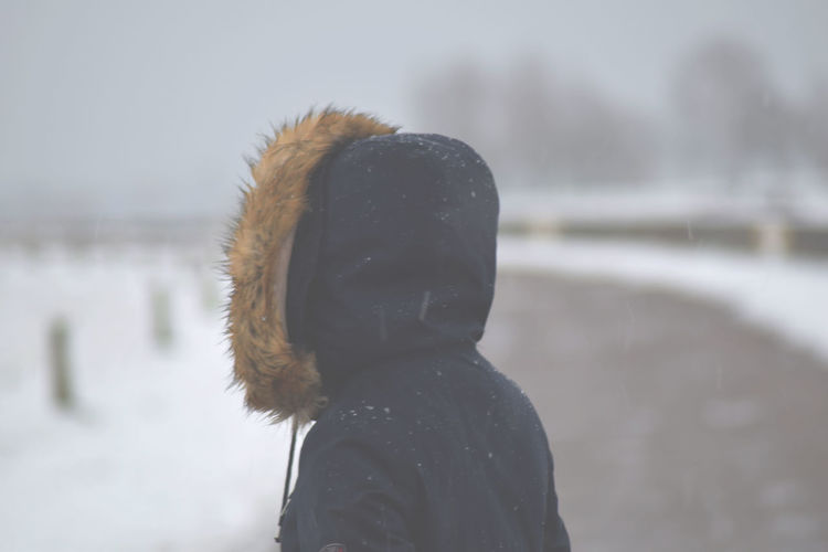 Close-up of woman on road during snowfall