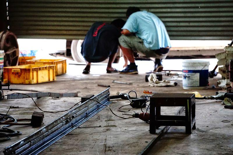 Rear view of mechanics working in repair shop