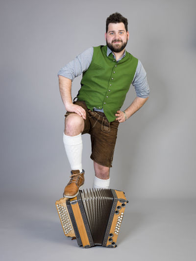 young man with black beard and leather trousers and traditional costume and accordion is posing in front of grey background Musician Costume Leather Trousers Tradition Traditional Austria Green Pose Accordion Man Young Shorts Friendly Proud Happy Play Music Fun Joy Single One Background Copy Space Studio Entertainment Mountains Shirt STAND Hobby Leisure Cool Studio Shot Portrait One Person Casual Clothing Full Length Looking At Camera Indoors  Standing Young Men Front View Young Adult Gray Background White Background Lifestyles Smiling Adult Gray Beard