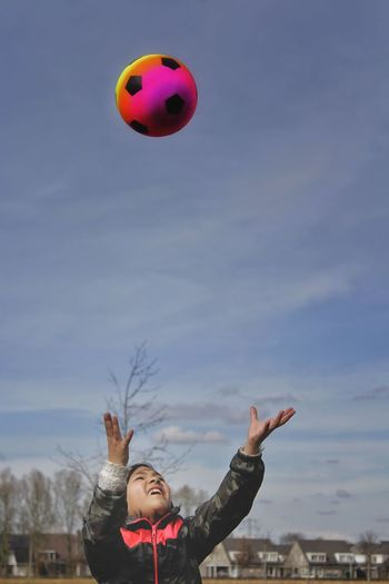Cute girl with arms raised looking at soccer ball against sky