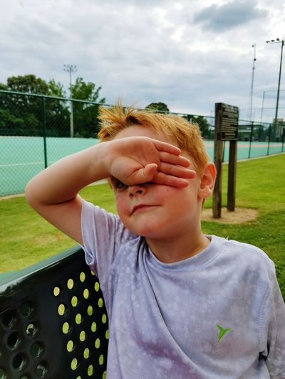 Cute boy covering face with hand by tennis court against sky