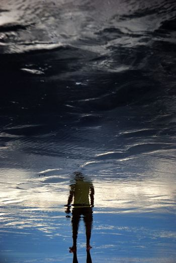 Upside down image of man reflecting in puddle