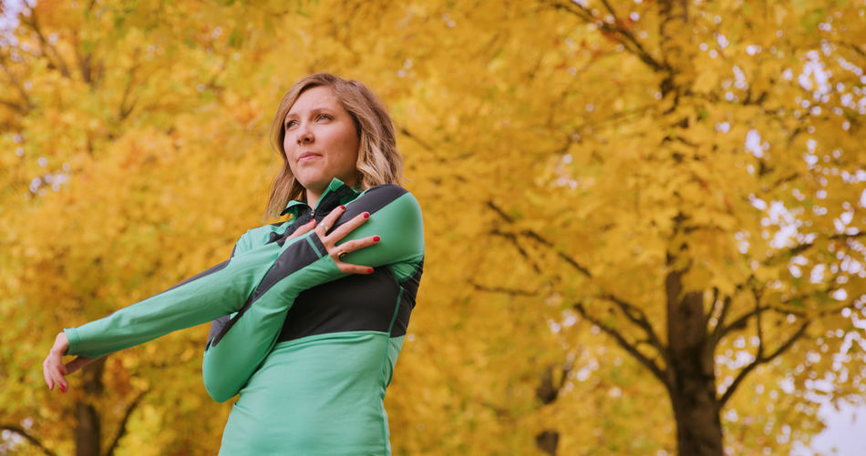 Young woman stretching arm in park during autumn