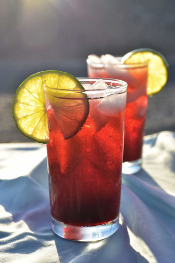 Glasses of hibiscus flower petal iced tea with lime slice garnish in hot sunny mojave desert setting