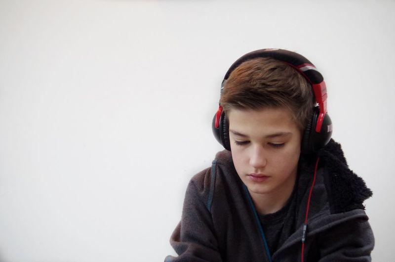 Boy listening music against white background