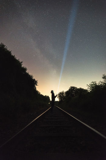 Silhouette Person With Illuminated Flashlight Standing On Railroad Track Against Sky At Night