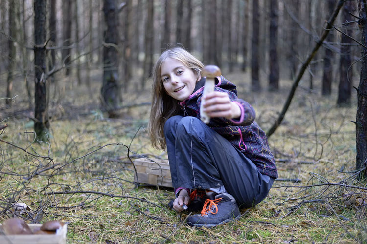 Portrait Of Smiling Cute Girl Collecting Edible Mushroom In Forest