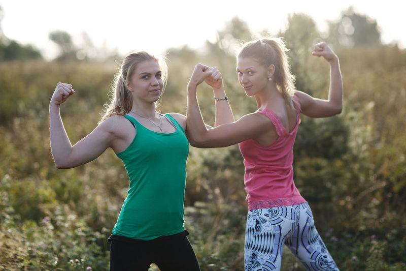 Portrait Of Friends Flexing Muscles On Field