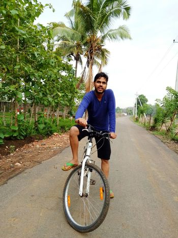 Bicycle Only Men One Man Only Cycling Adults Only Adult One Person Smiling One Young Man Only Casual Clothing Young Adult People Transportation Happiness Portrait Looking At Camera Road Fun Men Day Live For The Story