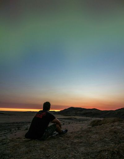 Rear view of man sitting on land against sky during sunset