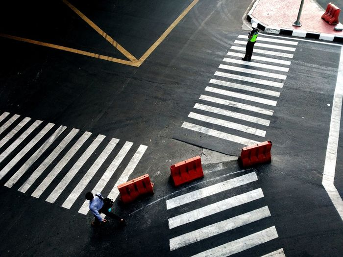 High angle view of officer standing on zebra crossing at street