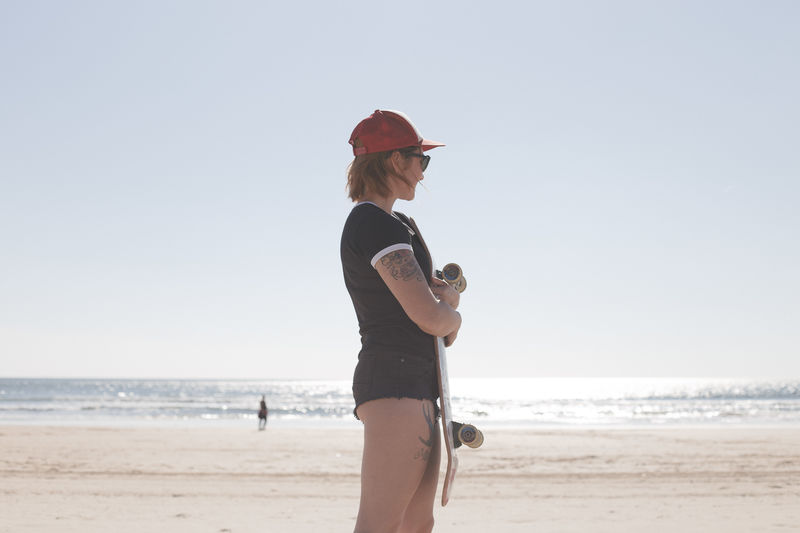 Side View Of Young Woman Standing On Beach Against Clear Sky