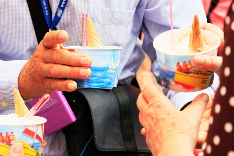 Close-up of people holding gelato in disposable cup